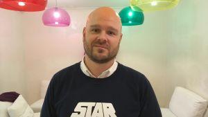 Andy Prinkkilä står i ett rum där färgglada lampor hänger från taket. Han bär en tröja med en star wars logo på sig.