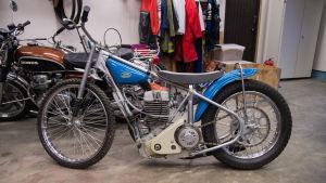 En blå speedwaymotorcykel av märket Jawa.