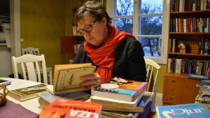 Kvinna sitter och bläddrar i en bok.