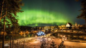 Väldigt norrsken över gammal stad.