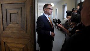 Juha Sipilä i riksdagens korridorer med journalister.