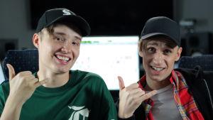 Isac Elliot och Christoffer Strandberg sitter i en studio. Christoffer är utklädd till Isac. De har båda två på sig en svart keps.