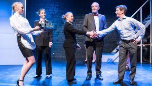 Läkaren Rurik (Markus Haakana, längst till höger) välkomnas till Raseborg av tre tjänstemän i kostym. Till vänster syns en servitör med en bricka med glas.