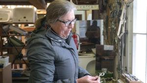 Kvinna håller gammalt fönsterhandtag i handen.