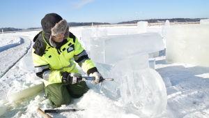 En man gör en isskulptur som föreställer en motorcykel
