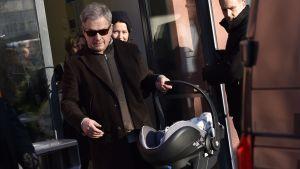 President Niinistö bär sin nyfödde son ut från Kvinnokliniken.
