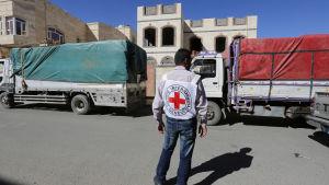 En biståndsarbetare för internationella Röda korset övervakar en biståndskonvoj i Sanaa.