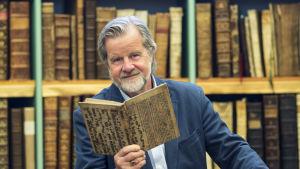 En man iklädd blå kavaj står framför en bokhylla. Han har grått hår och skägg, och håller en bok i handen.