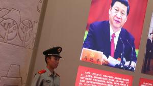 En polis står vakt vid en affisch med presiden Xi Jinping