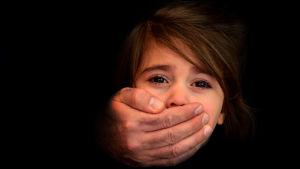 En stark manshand täcker en liten flickas mun.