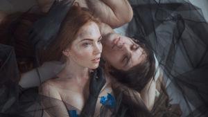 Taiteellinen kaksoismuotokuva miehestä ja naisesta makaamassa mustan harson keskellä.