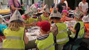 Dagisbarn som sitter runt ett bord och pysslar iklädda refläxvästar.