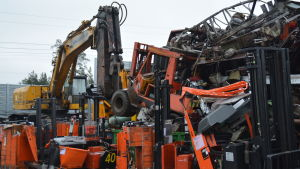 Stora mängder metallskrot väntar på att få krossas. I mitten en gammal röd traktor som ska krossas.