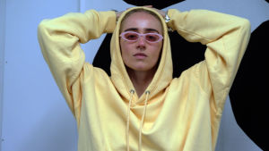 Den svenska hiphop-artisten Silvana Imam sitter med händerna bakom huvudet, hon har på sig en gul munkjacka.