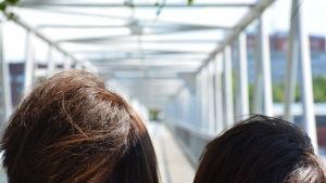 Två mörka huvuden tittar framåt längs bro med järnräcken