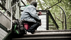 Kille i en trappuppgång på huk med kaffemugg i handen.