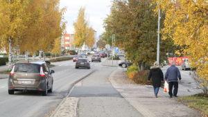 Ett äldre par går på gatan. På vägen till vänster om paret kör flera bilar.