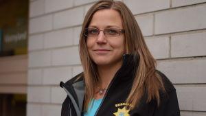 Ett foto av Sabina Friman som står vid en tegelvägg.
