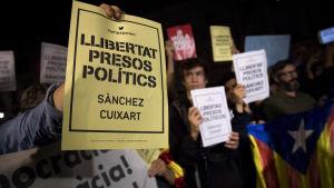 """Demonstranter i Spanien protesterar mot häktandet av två framstående katalanska separatister. Demonstranter håller fram papper med texten """"Libertat presos políticts""""."""