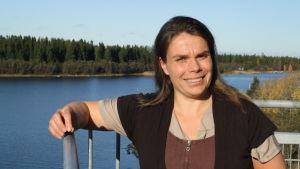 Johanna Vuorinen står och lutar mot ett räcke uppe i ett gammalt sjöbevakningstorn i Kristinestad. I bakgrunden syns havet och öar.