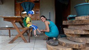 Italiensk kvinna rättar till pojkes en sandal