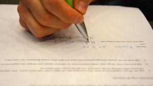 Hand som skriver under ett papper.ö