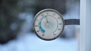 En termometer visar 5 minusgrader mot en snöig bakgrund.