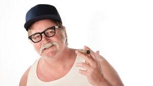 Vit man med mustasch  i wifebater-undertröja med keps och cigarr. En så kalad redneck.