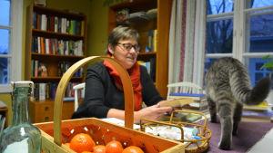 Kvinna sitter och bläddrar i en bok vid ett bord med mandariner och en katt.