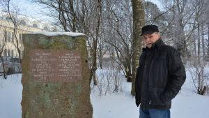 Eero Luomala bredvid minnesstenen över de avrättade som skall flyttas högre upp i Skolparken