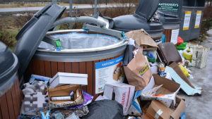 Stora avfallsbehållare med skräp utanför.