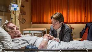 man ligger i koma på sjukhussäng med dottern bredvid på besök.