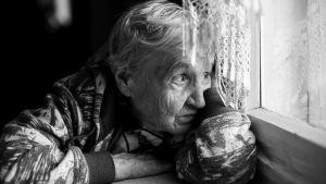 Äldre dam ser ut genom fönstret. Svartvit bild.