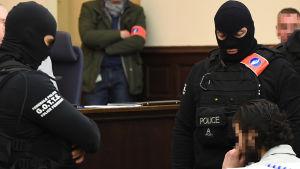 Den huvudmisstänkta Salah Abdeslam (till höger) sitter omringad av  belgiska specialstyrkor i rättegångssalen strax innan rättegången ska inledas.