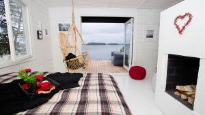 En lyxig stuga med öppen dörr och vy över havet.