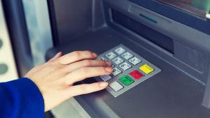 Hand knäpper in pinkod på bankautomat