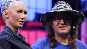 Grundaren och CEO av SingularityNET Ben Goertzel  talar med humanoiden Sophia, den första roboten som fått medborgarskap i Saudi Arabien. Det skedde under the 7th Web Summit i Lissabon, 07.11.2017.