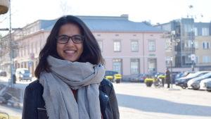 En bild på en kvinna i halsduk som ler. I bakgrunden syns ett torg.