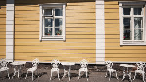 På utsidan av handelshuset. Vita bord och stolar i solskenet framför handelshusets gula vägg.