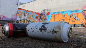 Två tomma sprayfärgsburkar ligger framför en vägg prydd av graffiti.