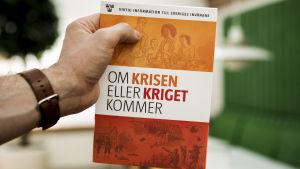"""En hand håller upp en broschyr med texten """"om krisen eller kriget kommer""""."""