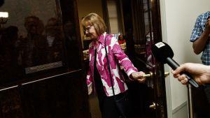 Annika Lapintie i Marimekkokavaj stänger dörren till grundlagsutskottets vårdreformsmöte.