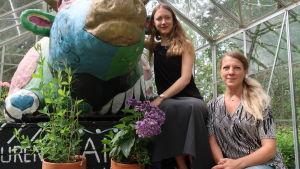 Två kvinnor sitter intill en konstnärlig och färgrann koskulptur inne i ett växthus.