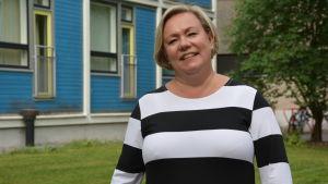 Pirjo Lipponen-Vaitomaa framför de gamla blåa bostadshusen i studentbyn