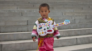 En liten pojke med leksaksgitarr i Pyongyang i Nordkorea