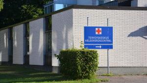 Hangö hälsocentral, en vit tegelbyggnad i 1-2 våningar. Soligt väder, grönt gräs. En blå skylt där det står Terveyskeskus Hälsovårdscentral.