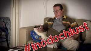 En man sitter i soffan och tittar på tv.