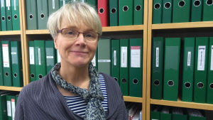 Rektor för Winellska skolan, Kristiina Koli, står framför en hylla med gröna mappar och ser glad ut.