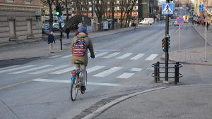En cyklist med färggrann ryggsäck cyklar över Aurabron mot Åbo centrum.