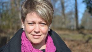 En porträttbild utomhus av Jeanette Pajunen somn är social- och hälsovårdsdirektör i Raseborg.